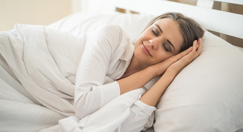 Woman sleeping soundly in bed after smoking the best indica strains from Stok'd cannabis dispensary in Scarborough, ON.